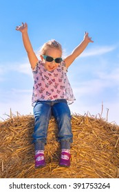 A girl sitting on a bale of straw rising her arms