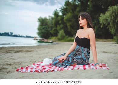 Girl sitting on the beach alone and looking far away on a cloudy day