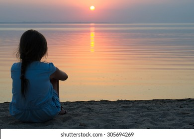 girl sitting on the beach in a light summer dress, watching the sun set into the sea on the horizon