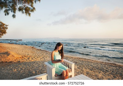 Girl sitting on the beach and reading a book