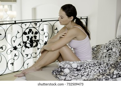 Girl is sitting on the bed, she is sorrow or she feel bad.