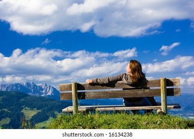 Girl sitting on a bench over blue sky