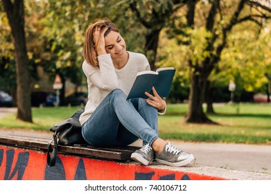 Girl sitting on bench in park and reading book.