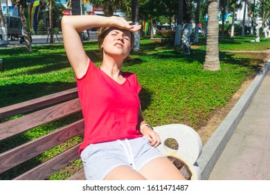 Girl sitting on the bench, suffering from heat, woman with heatstroke. Having sunstroke at summer hot weather. Dangerous sun, girl under sunshine. Headache, feeling bad. Person holds hand on head