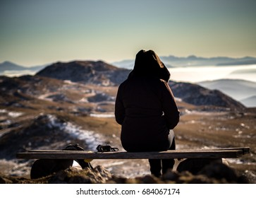 Girl Sitting on bench on top of mountain