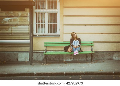 Girl sitting on a bench and waiting for the public transportation.