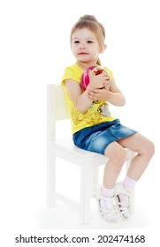 girl sitting on a chair and hugs ball looking to the side.passionate child for interesting occupation,active lifestyle,happiness concept,carefree childhood concept.