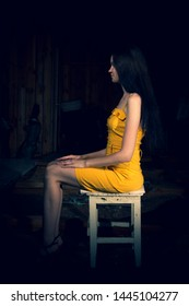 The girl is sitting on a chair in a yellow dress in a dark, old room.