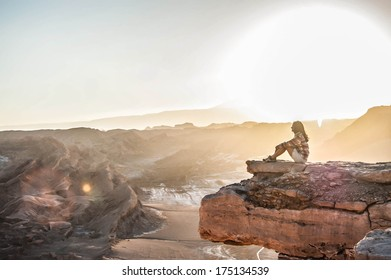 Girl sitting on cliff edge