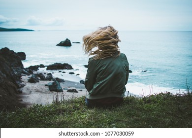 girl sitting on a cliff overlooking the ocean with her hair blowing
