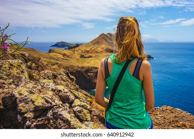 Girl sitting on a cliff overlooking a house on a cliff in Madeira with Atlantic ocean in the background