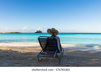 The girl sitting on a deck chair on a sandy beach and looking into the distance.
