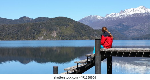 girl sitting on a dock by the lake, Patagonia, Argentina