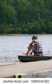Girl sitting on a dock at a local lake, enjoying the peacefulness & views in  country setting hoping for a friend