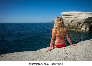 The girl sitting on the edge of a cliff, Sarakiniko beach, Milos