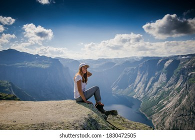 Girl sitting on the edge of a rocky cliff. Extreme tourism. Mountains and fjords of Norway. A tourist in a white cap on a cliff looks at the scenery