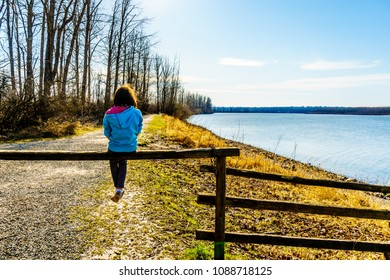 Girl sitting on a fence on the Matsqui Dyke along the Fraser River between the towns of Abbotsford and Mission in British Columbia, Canada