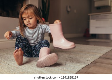 Girl sitting on the floor at home and putting on boots.