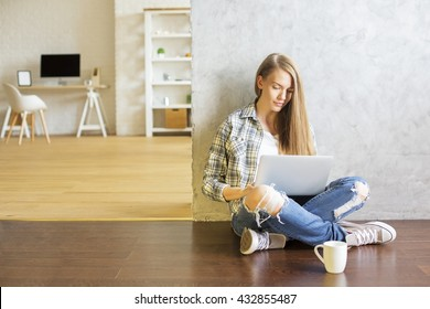 Girl sitting on floor in interior next to coffee cup and using laptop