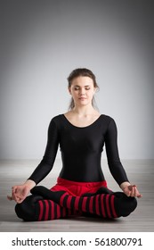 girl sitting on the floor and meditating in the lotus position