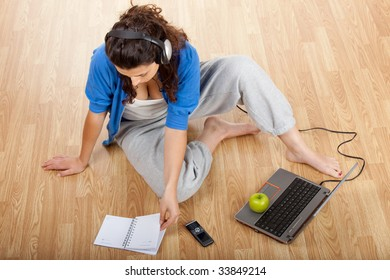 Girl sitting on floor and working with a laptop