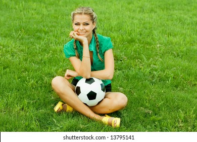 A girl sitting on a football field with a ball.