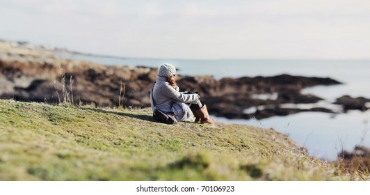Girl sitting on the grass of a cliff, watching the horizon