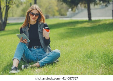 Girl sitting on the grass with coffee and tablet on the street.