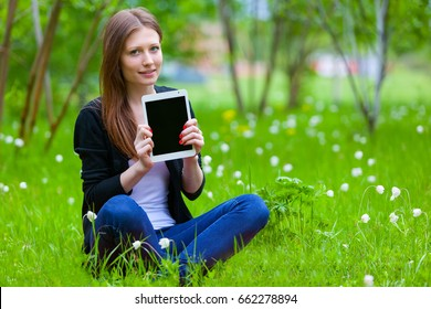 A girl sitting on the grass holding a tablet computer