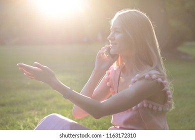 Girl sitting on the grass in the park and talking on the phone at sunset