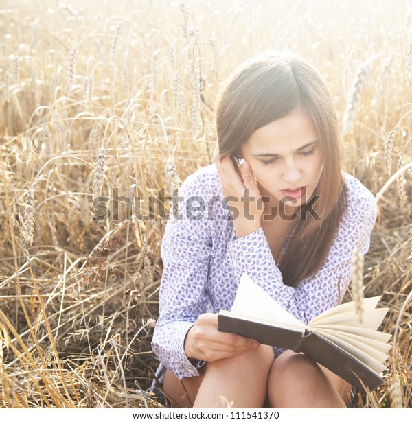 The girl sitting on a grass, reading a book