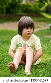 girl sitting on a grass with wounds and scratches on her knees