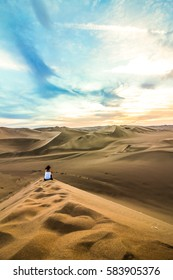 Girl sitting on the great dunes of the desert, contemplating the tranquility.