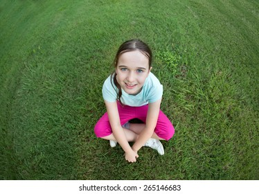 A girl sitting on the green grass looking up at the camera