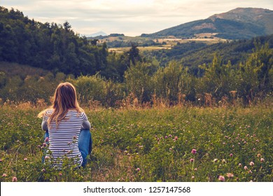 Girl sitting on a green meadow and watching the countryside landscape.