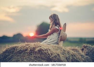 Fille assise sur une botte de foin et admirant le coucher du soleil