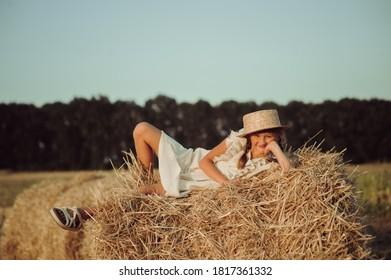 Fille assise sur une botte de foin dans un chapeau de paille dans le champ