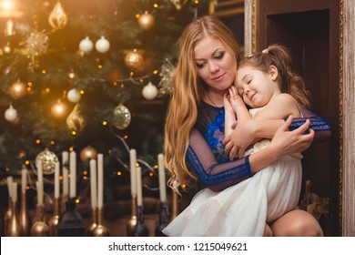The girl is sitting on his mother's lap on a background of a Christmas tree and a fireplace. Waiting for a holiday. Many candles under the tree
