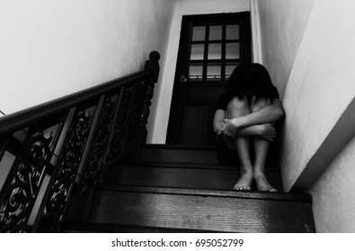 Girl sitting on ladder in house with arm around knee and lower head in white tone