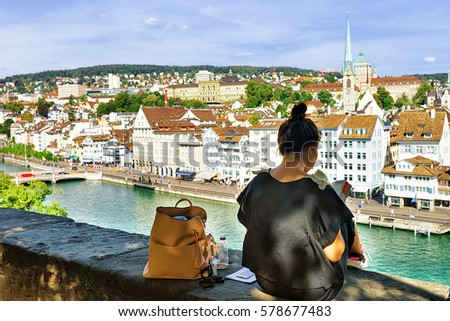 Girl sitting on Lindenhof hill and looking into a guide book in Zurich, Switzerland. Limmatquai and Predigerkirche on the background