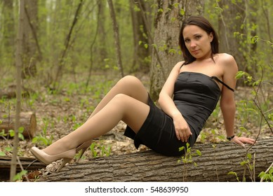 Girl sitting on a log in the spring forest