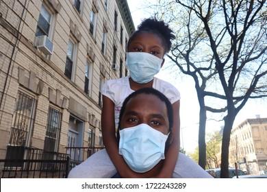Girl sitting on mans shoulders wearing blue surgical masks