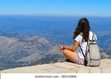 girl sitting on the Mount Lovcen in Montenegro among the clouds and look at the panorama of the mountains