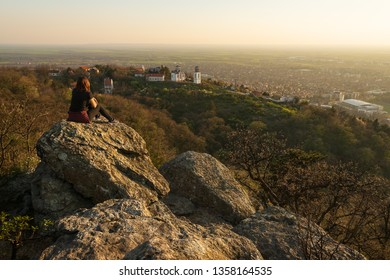 Girl sitting on mountain rock in sunset looking to horizon over small town Vrsac and white church on the top of the hill,