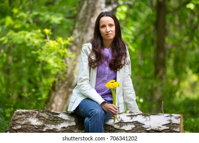 Girl sitting on a Park bench with a bouquet of dandelions
