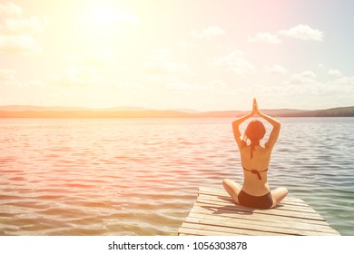 The girl is sitting on the pier and doing yoga. Against the background of blue mountains and water (lake, ocean, sea) - Shutterstock ID 1056303878