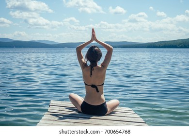 The girl is sitting on the pier and doing yoga. Against the background of blue mountains and water (lake, ocean, sea)