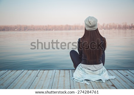girl sitting on pier lookingat river の写真素材 今すぐ編集