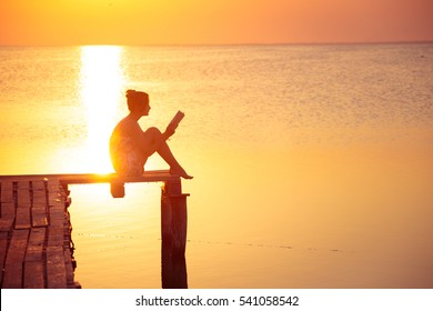 girl sitting on a pier and reading at the sunset time