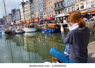 girl sitting on a pier and taking a shot of Honfleur harbor with her smartphone